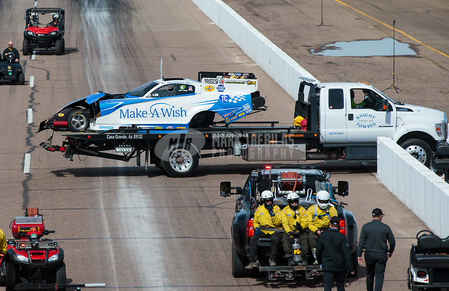 Feb 24, 2019; Chandler, AZ, USA; The car of NHRA funny car driver Tommy Johnson Jr is towed back to the pits by a flatbed tow truck after losing a rear tire after an axle failure and explosion during the Arizona Nationals at Wild Horse Pass Motorsports Park. Johnson was uninjured. Mandatory Credit: Mark J. Rebilas-USA TODAY Sports