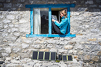 A woman trekker inside her guesthouse sits above her solar panels, Nepal