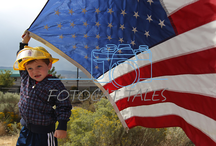 Janson Ross, 4, of Carson City, rallies outside the Nevada National Guard facility in Carson CIty, Nev., on Sunday, Sept. 11, 2011. Three Guard members killed earlier this week by a gunman in an IHOP restaurant are honored during a private memorial. (AP Photo/Cathleen Allison)