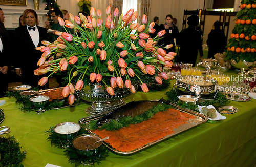 """Washington, D.C. - November 30, 2005 --  First lady Laura Bush announced """"All Things Bright and Beautiful"""" as the theme for the 2005 holiday season at the White House in Washington, D.C. on November 30, 2005.  The grand buffet table in the State Dining room has a floral centerpiece of orange tulips sitting on a lime-green taffeta tablecloth with a matching overlay lined in vivid orange.  A Smoked Salmon Display with Yukon Potato Crepes, Chive Crème Fraiche, and Red Onion Marmalade is seen in the forground..Credit: Ron Sachs / CNP"""