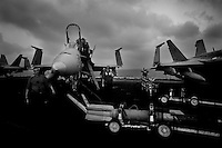 Crew aboard the flight deck of the USS Dwight D. Eisenhower (CVN 69), load weapons on fighter jets which in a few hours are going to fly over Afghanistan to support ground troops in air to ground bombing missions on Monday June 1 2009 at an undisclosed location in the Arabian Sea. .The ship is a nuclear powered american aircraft carrier that is currently supporting Operation Enduring Freedom, the american effort in Afghanistan, by sending tens of its jets every day to support ground troups in air to ground bombing operations.