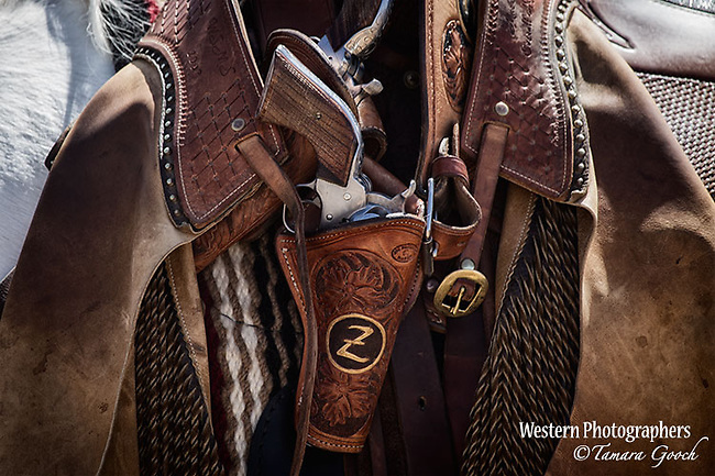 A photo of a mounted shooters guns, holsters and chaps haning over the saddle on their horse.