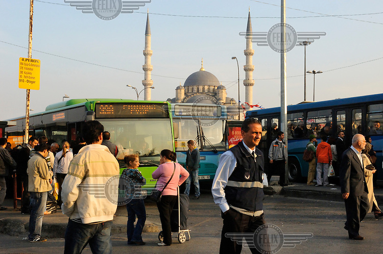 A bus station at Eminonu, with Yeni Cami mosque rising beyond.
