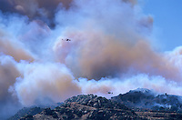 870000394 two los angeles county fire fighting helicopters fly over a burning hillside in the path of the topanga fire in the hills above the san fernando valley in southern california