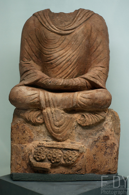 Headless statue of Buddha seated on throne in meditation posture. Dated 5-7th century AD, found in Tepe Sardar, Ghazni Province, Afghanistan. Kabul National Museum