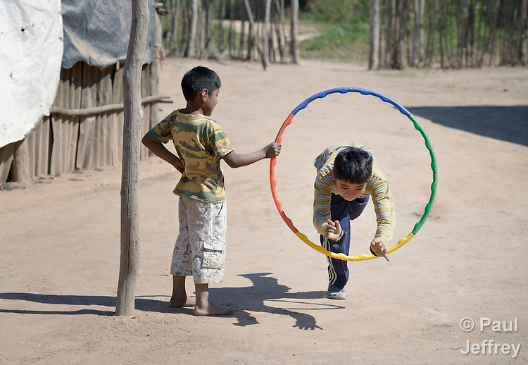 Juan Lovenzo, a 9-year old Wichi indigenous boy, leaps through a hoop held by Hiquino Cristobal in Lote 75, an indigenous neighborhood of Embarcacion, Argentina. The Wichi in this area, largely traditional hunters and gatherers, have struggled for decades to recover land that has been systematically stolen from them by cattleraisers and large agricultural plantations.