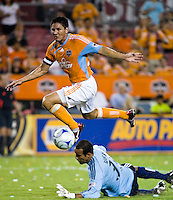 Houston Dynamo forward Brian Ching (25) takes a shot over the top of D.C. United goalkeeper Josh Wicks (31).  Houston Dynamo defeated D.C. United 4-3 at Robertson Stadium in Houston, TX on August 1, 2009.