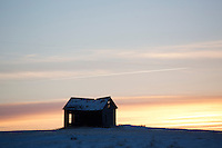 An abandoned shack sits atop a hill on the Montana Hi-Line in northern Montana, USA.