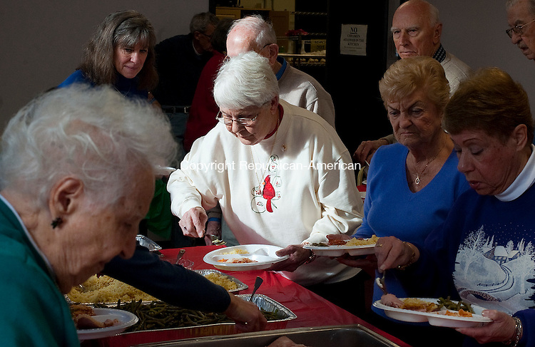 WINSTED,  CT-122816JS02-- Luncheon guests, including Carol Rose of Winsted, center, dish up food during Wednesday's senior parishioners luncheon held at the st. Joseph Church Parish Center in Winsted.  The meal was prepared by Phyllis Wells and parish volunteers.   More than 70 parishioners attended the luncheon, which is held twice a year, and is made possible through a grant through the Cooperative Parish Sharing, Social Justice<br /> Ministry of the Archdiocese of Hartford.<br /> Jim Shannon Republican-American