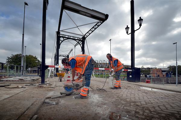 VIANEN - In Vianen zagen medewerkers van Bowa Bestrating met water, stenen op maat tijdens het aanbrengen van nieuwe bestrating rondom de Grote Sluis. In opdracht van de provincie Zuid-Holland, die als vaarwegbeheerder van het hele Merwedekanaal ook verantwoordelijk is voor deze sluis in de provincie Utrecht, zijn eerde de sluisdeuren vervangen en de aandrijvingen vernieuwd en wordt nu ook de toegankelijkheid tot de bruggen verbetert. COPYRIGHT TON BORSBOOM