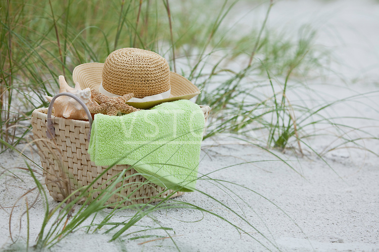 USA, Florida, St. Pete Beach, Basket with straw hat, towel and shells on beach