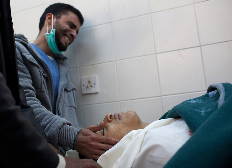 Nasser Abdul Faly touches the face of his brother Abdullah, 18, killed during fighting between opposition rebels and loyalist forces of Col. Muammar Qaddafi, in Benghazi, Libya, March 20, 2011. Abdullah was shot as Qaddafi forces entered the Thabalin neighborhood of Benghazi. The main hospital in Benghazi reported around 50 dead fighters and civilians the previous day and at least 35 on Sunday.