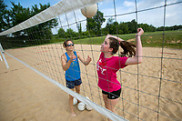 NWA Democrat-Gazette/JASON IVESTER<br /> Christina Lawrence, volleyball coach, tosses a ball to Taylor Voigt, 13, of Lowell on the sand volleyball court Wednesday, June 14, 2017, at Kirksey Middle School in Rogers. Lawrence was working with Taylor and Lindsey Grace Allen, 13, of Rogers on summer volleyball workouts.