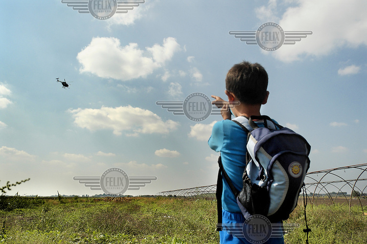 A Syrian refugee boy pretends to shoot a Hungarian police helicopter as he stands in the border reception camp near Hungarian-Serbian border.<br /> <br /> Hungary, along with Italy and Greece, has seen a huge influx of refugees and migrants in 2015. Most of them cross the border into Hungary from neighbouring Serbia and usually intend to travel onwards to Austria, Germany or other northern European countries where they hope to claim asylum and find employment. Due to the large numbers of people entering the country illegally, Hungary has built a 175 km long, 4 metre high fence along its southern border with Serbia to try and keep them out. It has also announced that from Tuesday 15 September 2015 anyone crossing into Hungary illegally will be arrested and put in prison rather than being taken to a refugee camp.