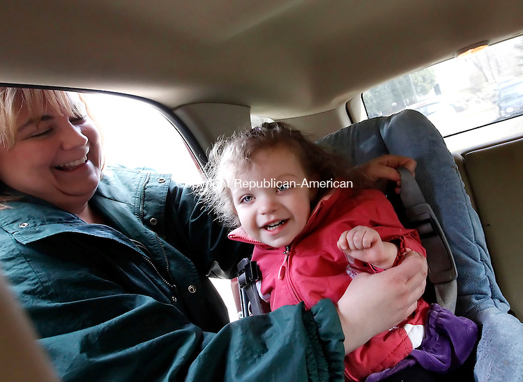 Waterbury, CT- 25, March 2011-032511CM03 Michelle Harris secures her daughter, Kaylee, who is almost 2 1/2, in her car seat at Country Garden Daycare in Waterbury Friday afternoon.  The American Academy of Pediatrics recently announced a revision of it's car safety guidelines for children.    Christopher Massa Republican-American