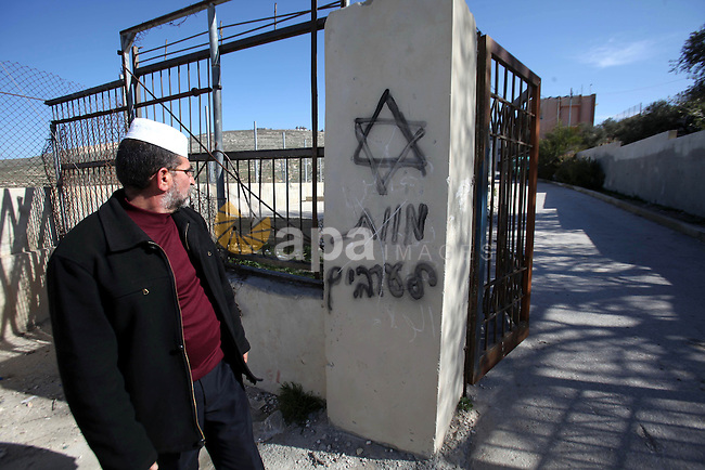 "A Palestinian man stands near a graffiti reads ""death to Arab"" including a Star of David, sprayed on the wall of a school in the Village of Urif by Israeli settlers, near the West Bank city of Nablus, February 26, 2015. There were at least 329 incidents of settler violence against Palestinians in the occupied West Bank in 2014, according to the UN Office for the Coordination of Humanitarian Affairs. Photo by Nedal Eshtayah"