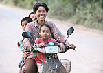 Binn Im, driving her motorcycle, is the Methodist pastor in the Cambodian village of Pheakdei.