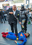 Manhattan, New York City, New York, USA. October 10, 2015. Cosplayers Wilson Alexander Luthor the Kingpin laughs evilly as he steps on Superman, as Bathman looks on, at the 10th Annual New York Comic Con. Batman, played by PAUL from NY, was dragging the Superman stuffed dummy by a rope. NYCC 2015 is expected to be the biggest one ever, with over 160,000 attending during the 4 day ReedPOP event, from October 8 through Oct 11, at Javits Center in Manhattan