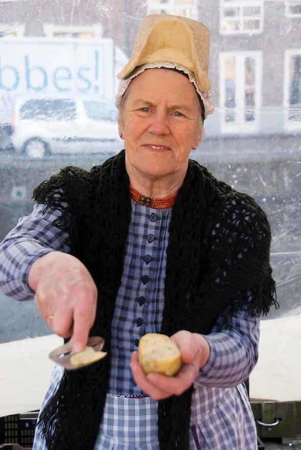 Alkmaar, 2 april, 2010.Binnenstad van Alkmaar.Kaas verkoopster geeft plakje kaas om te proeven. . (c)Renee Teunis.
