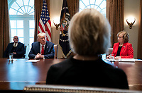United States President Donald J. Trump, left, speaks to Debbie Hatmaker, right, Chief Nursing Officer of the ANA Enterprise, as he holds a meeting with nurses on the COVID-19 response at the White House in Washington, DC, March 18, 2020, in Washington, DC.  Director of the Centers for Disease Control and Prevention Dr. Robert Redfield looks on from the left. <br /> Credit: Kevin Dietsch / Pool via CNP/AdMedia