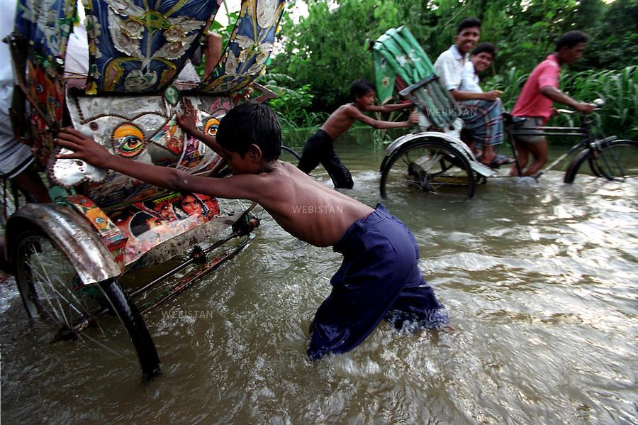 2004. Children push rickshaws on a flooded road in Badda, an area about 4 Km from downtown in Dhaka. Des enfants poussent des rickshaws sur une route inondée à Badda, un quartier à 4 Km du centre ville à Dacca.