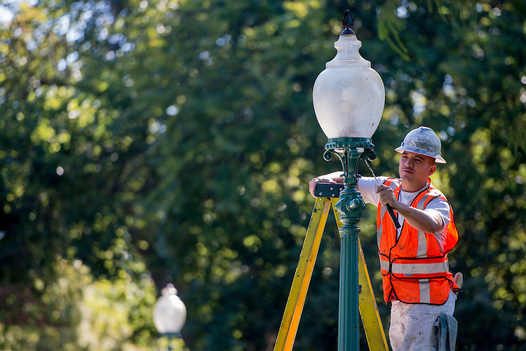 UNITED STATES - SEPTEMBER 10: Architect of the Capitol worker Francisco Arevalo applies a fresh coat of paint to one of the lamps lining a walkway on the east front of the Capitol on Monday, Sept. 10, 2012. (Photo By Bill Clark/CQ Roll Call)