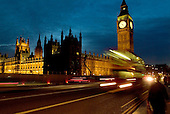 Traffic sweeps past Big Ben and the Houses of Parliament