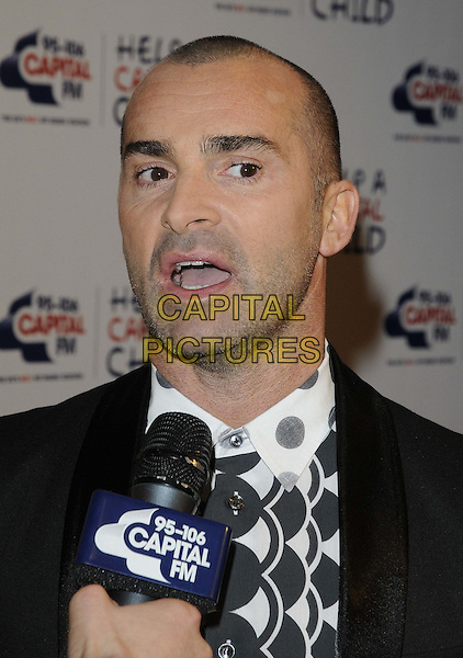 Louie Spence.The Capital Rocks fundraising event in aid of the Help A Capital Child charity, The Roundhouse, Chalk Farm Rd, London, England..November 29th, 2012.headshot portrait microphone stubble facial hair black white shirt jacket print  mouth open .CAP/CAN.©Can Nguyen/Capital Pictures.