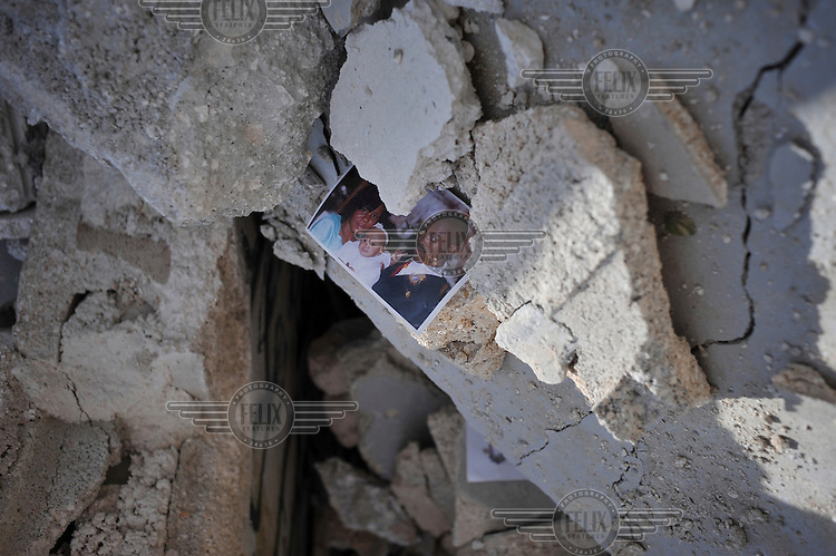 A family photograph lies amid the debris of a collapsed house five days after the earthquake hit Port-au-Prince..A 7.0 magnitude earthquake struck Haiti on 12/01/2010. Early reports indicated that more than 100,000 may have been killed and three million affected.