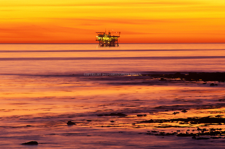 Platform Holly, an off-shore oil drilling platform, at sunset. Platform operates in 211 ft (64m) of water roughly two miles southwest of Coal Oil Point, working the Ellwood Oil Field in the Santa Barbara Channel. Built by ARCO in 1966; owned and operated by Venoco, Inc. Santa Barbara County, CA.