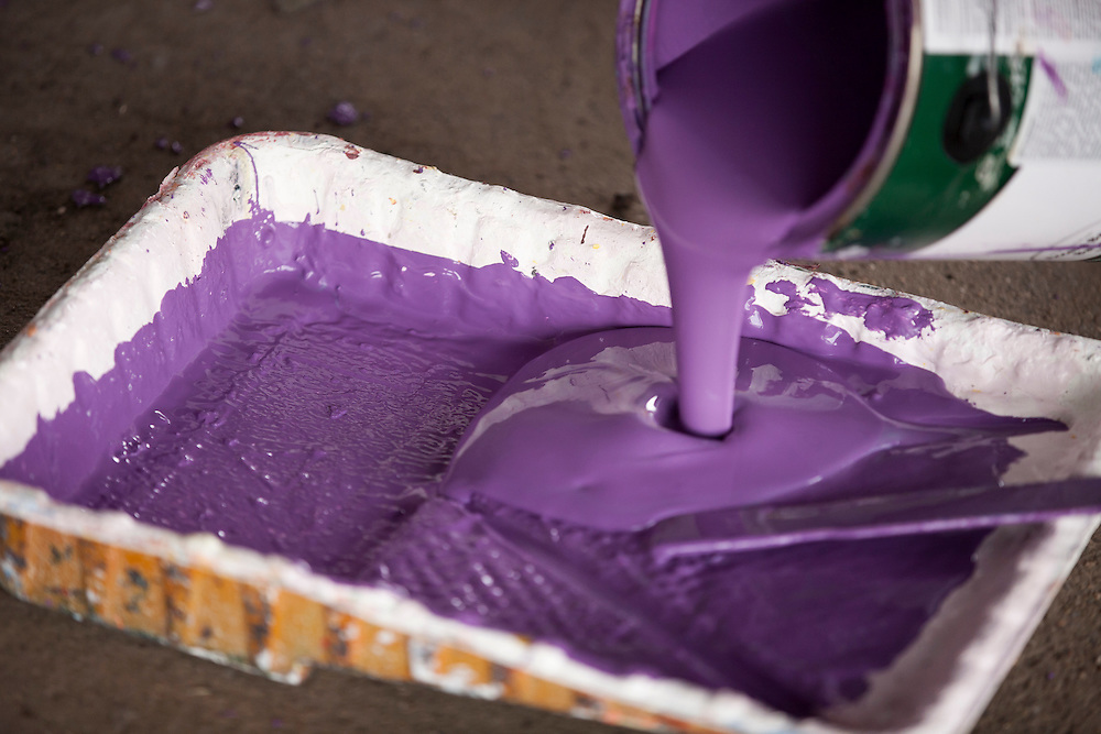 """Members pour a bucket of purple paint as they prepare to paint under a train bridge during """"Circle the City with Service,"""" the Kiwanis Circle K International's 2015 Large Scale Service Project, on Wednesday, June 24, 2015, in Indianapolis. (Photo by James Brosher)"""