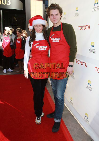 JENNIFER LOVE HEWITT & ALEX BEH .Christmas Eve For Homeless Served at Los Angeles Mission held At The Los Angeles Mission, Los Angeles, CA, USA..December 24th, 2010.full length red hat white shirt turtleneck polo apron couple jeans denim green jumper sweater  .CAP/ADM/KB.©Kevan Brooks/AdMedia/Capital Pictures.