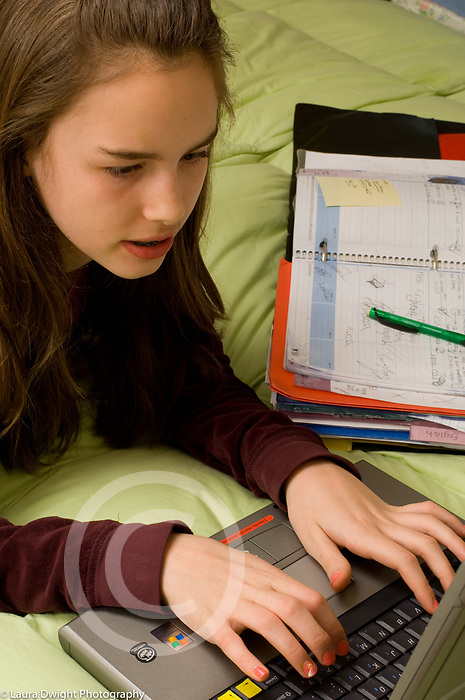 Teenage girl age 13 in bedroom doing homework on bed using laptop computer