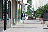 Attractive female shopper holds shopping bags and walks down the sidewalk at an Austin outdoor shopping center