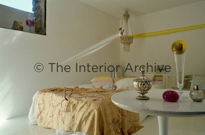 The guest bed is draped in an antique gold textile and has a free-standing bath behind it