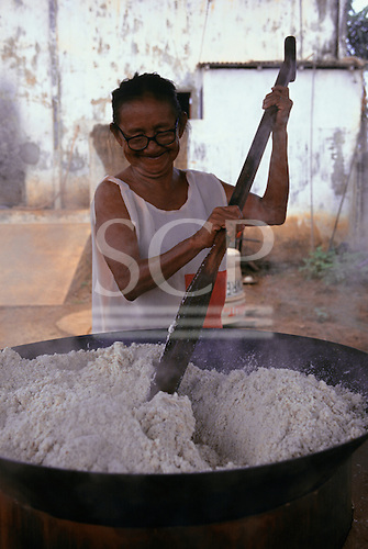 Altamira, Amazon, Brazil. Amazoncoop brazil nut oil factory; Dona Xipaya cooking nuts in a large pan before extracting the oil.
