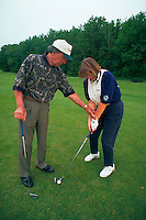 Golf pro giving a woman golfing lessons, demonstrating the correct way to hold the golf club.