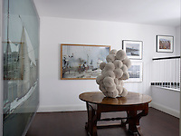 Artworks displayed on the walls of the upstairs gallery, from left, Jeff Wall, Subodh Gupta, Alec Soth (top), Stephen Shore, and Joel Sternfeld and the Biedermeier hall table displays a sculpture made of paper plates by Tara Donovan