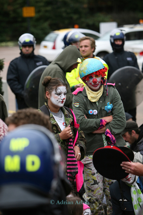 Climate change protesters,many dressed as clowns, at Climate Camp, Heathrow.  Contained  by riot police near the BAA offices.<br /> 2,000 protesters gathered at an impromptu camp set up to protest against the UK's airport expansion program.