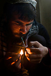 Ruhollah, 25, an Afghan refugee returnee from Iran, smokes heroin at the former Russian Cultural Center, Kabul, Afghanistan, Apr. 9, 2009. In addition to the 650 drug addicts who reside at the cultural center, an estimated 1500 more people go there to buy and use drugs. The United Nations Office on Drugs and Crime emergency detox center began operating at the end of January 2009 to stem the daily deaths occurring among the drug-addicted population living on the sprawling cultural center grounds. The detox center is the largest ad-hoc drug treatment center in Afghanistan, serving 650 residents with a daily hot meal, detoxification assistance, medical aid and counseling.