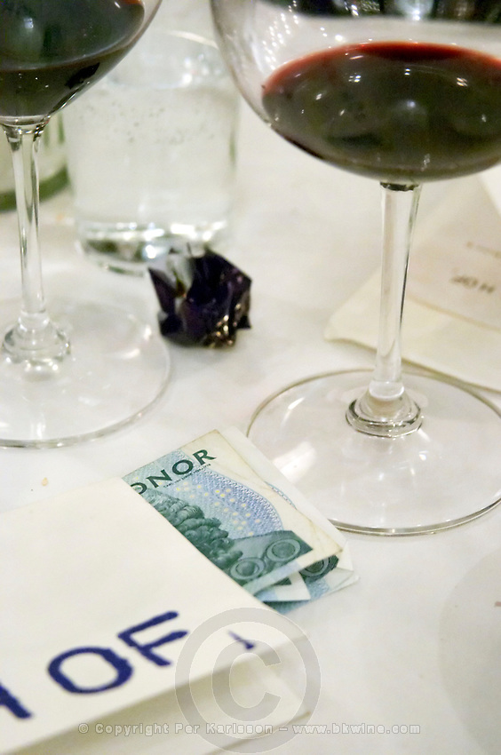 Sture Hof, a classic French style bistro and wine bar. The restaurant bill in a fold with money to pay for the meal sticking out. An almost empty wine glass. Stockholm. Sweden, Europe.