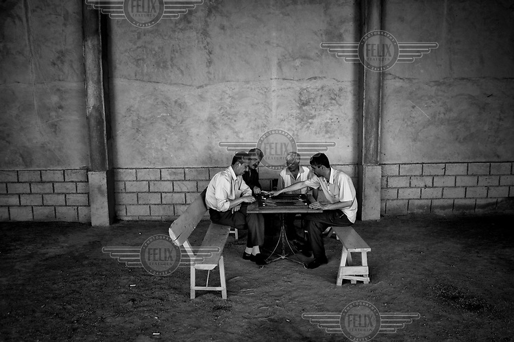Men play chess in an empty building. During the 1950s and the 1960s the rivers that feed the Aral Sea (the Amu Darya and the Syr Darya) were diverted for irrigating cotton and other crops. This caused the lake to shrink uncovering sediments heavily polluted with industrial fertilizers that were washed into the lake over the preceding decades. Without the lake's water to contain it these toxic particles were spread by the wind and have caused numerous health problems in surrounding communities. Furthermore, as the lake evaporated the remaining water became increasingly saline and unable to sustain life, destroying the fishing industry. Muynak, once a thriving fishing port, became a depressed and dusty town far from the receding shore.