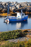 A blue fishing boat is moored behind the protective harbour wall