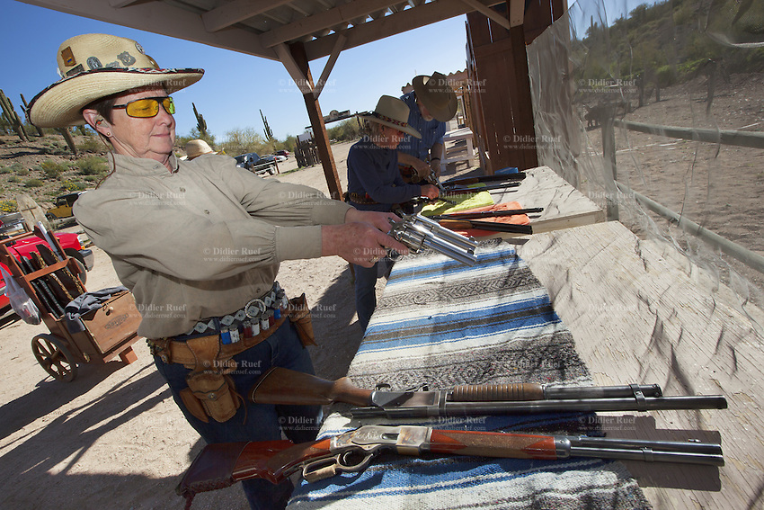 "USA. Arizona state. Peoria. Peoria is distant 50 km from Phoenix. Cowtown Shooting Range. Cowtown Cowboy Shooters Association. Fake town scenery from the old Far West time. A group of elderly women and men, all dressed with cowboys outfits, train outdoors for the incoming Winter Range - SASS National Championship of Cowboy Action Shooting ( february 22nd-28th, 2016). The Single Action Shooting Society (SASS) is a Cowboy Action Shooting (CAS, also known as Western Action Shooting, Single Action Shooting, or Cowboy 3-Gun). CAS is a type of multi-gun match utilizing a combination of pistol(s), rifle ( Winchester), and/or shotgun in a variety of ""old west themed"" courses of fire for time and accuracy. Participants must dress in appropriate theme or era ""costume"" as well as use gear and accessories as mandated by the respective sanctioning group rules. A CAS shooter engages a target with his lever-action rifle. Cowtown Shooting Range is a semi-private outdoor shooting range and firearms training facility. A firearm is a portable gun, being a barreled weapon that launches one or more projectiles often driven by the action of an explosive force. Most modern firearms have rifled barrels to impart spin to the projectile for improved flight stability. The word firearms usually is used in a sense restricted to small arms (weapons that can be carried by a single person). The right to keep and bear arms is a fundamental right protected in the United States by the Second Amendment of the Bill of Rights in the Constitution of the United States of America and in the state constitutions of Arizona and 43 other states. 31.01.16 © 2016 Didier Ruef"