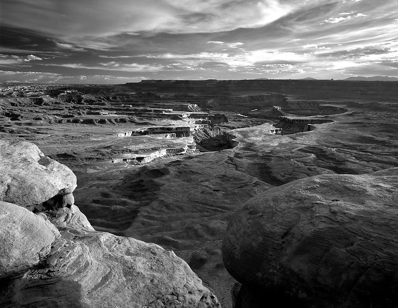Sun peeking through storm clouds at Green River Overlook. Canyonlands National Park. Utah.