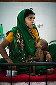 22 year old Radha Jitendra feeds her malnourished girl child, 12 month old Sangeeta Radha at the Nutrition Rehabilitation Centre (NRC) in Burhanpur district of Madhya Pradesh, India. Sangeeta was admitted to the NRC on Sept 17, 2012 and weighed 3.910Kg. Photo: Sanjit Das/Panos for ACF