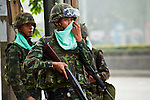 14 MAY 2010 - BANGKOK, THAILAND: A Thai soldier wipes his face during a break in street protests on Rama IV Rd Friday afternoon. Thai troops and anti government protesters clashed on Rama IV Road Friday afternoon in a series of running battles. Troops fired into the air and at protesters after protesters attacked the troops with rocket and small homemade explosives. Unlike similar confrontations in Bangkok, these protesters were not Red Shirts. Most of the protesters were residents of nearby Khlong Toei slum area, Bangkok's largest slum area. The running battle went on for at least two hours.   PHOTO BY JACK KURTZ