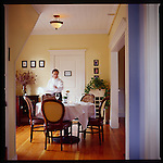 A waitress sets a table for 5 in preparation for dinner at The Painted Lady Newberg Oregon
