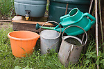 Watering cans and water butts and plastic bucket on allotment garden