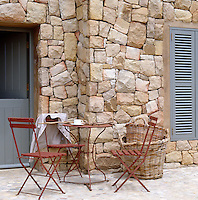 Wrought-iron garden chairs and a small table on a terrace beside the overscaled thick wall of natural stone with which this new property has been built